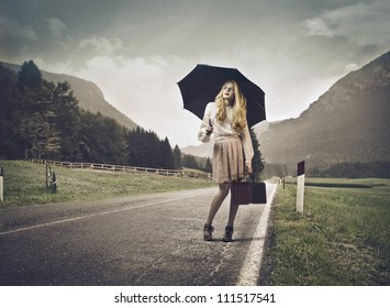 Young beautiful woman standing on a country street under an umbrella