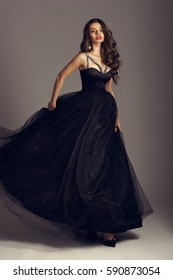 Young beautiful woman standing and posing in black ball gown on white gray background. Fashion style portrait of girl with long curly brunette hair.