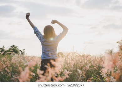 Young beautiful woman standing stretch her arms in the air on the grass field. Woman enjoy with nature during sunset.