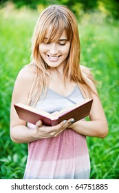 Young beautiful woman stands on green field and reads book.