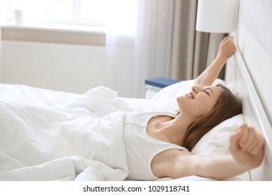 Young beautiful woman stretching in bed at home