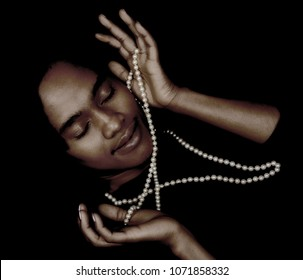 Young Beautiful Woman with a string of pearls on Black