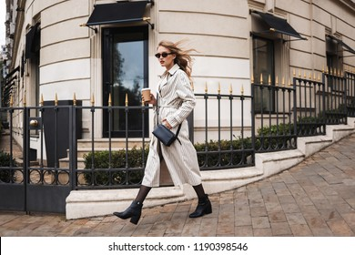 Young beautiful woman in striped trench coat and sunglasses with little black cross bag holding coffee to go in hand looking in camera walking around cozy city street