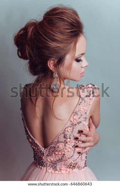 Young beautiful woman in stylish trendy pink long dress with jewelry - earrings and up do collected hair.
