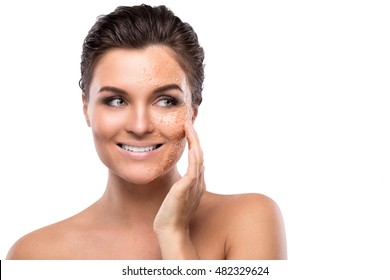 Young beautiful woman with sugar scrub on her face over white background