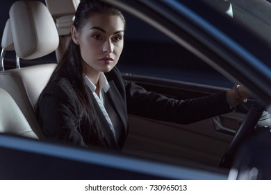 Young beautiful woman in suit sitting in a drivers seat of passenger car