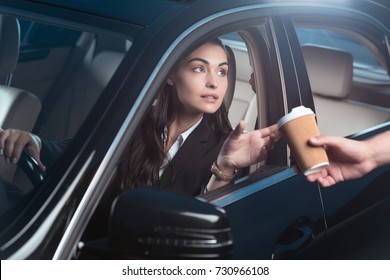 Young beautiful woman in suit sitting in driver seat of car and receiving coffee from drive-through employee
