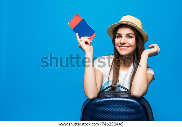 Young beautiful woman with suitcase holding passport on blue