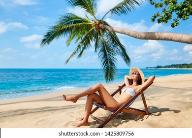 Young beautiful woman sunbathe and relax on tropical beach. Summer vacation concept