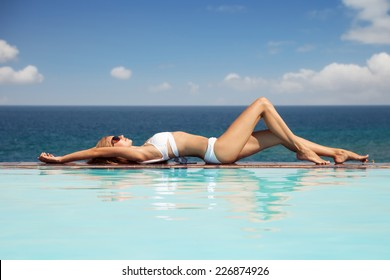 Young beautiful woman sunbathing. Nice sea view from swimming pool.