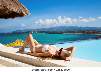 Young beautiful woman sunbathing. Nice sea view.
