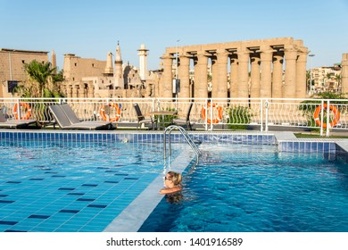 Young beautiful Woman sunbathing in swimming pool at luxurious looking on sunshade parasol in Egypt Luxor