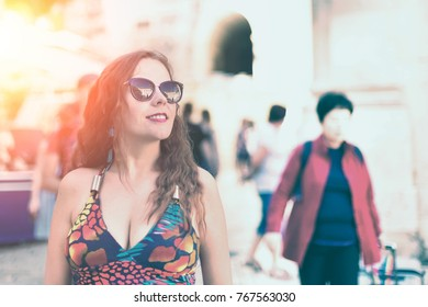 Young beautiful woman in sunglasses with curly hair. Street photo portrait.