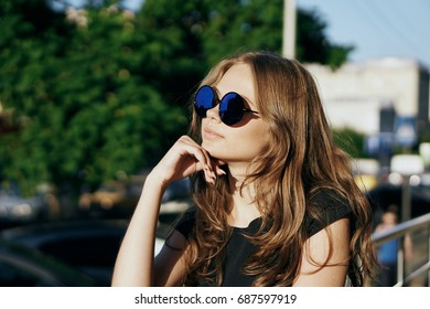 Young beautiful woman in sunglasses and with long hair walking along the street in the city, megapolis.