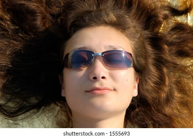 Young beautiful woman in sunglasses lying with spread hair in the sun