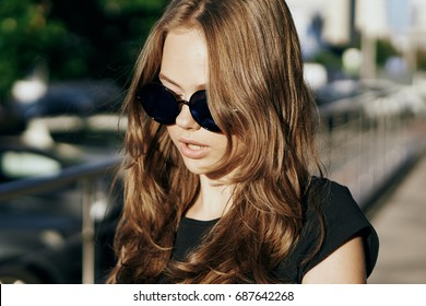 Young beautiful woman in sunglasses on the street in the city, megapolis.