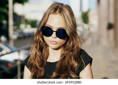 Young beautiful woman in sunglasses outside in the city, portrait.