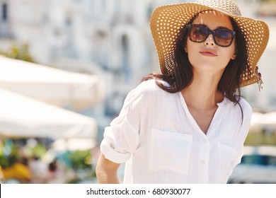 Young beautiful woman with sunglasses walking the streets of an Italian town