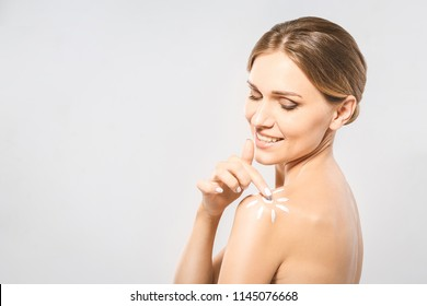 Young beautiful woman with sun-shaped sun cream. Pretty woman ready for suntan treatment. Sunscreen lotion sun drawing on woman shoulder. Isolated on white background.