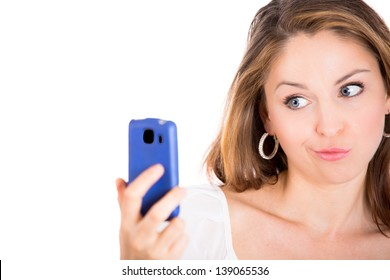 Young beautiful woman surprised by something on her cell phone