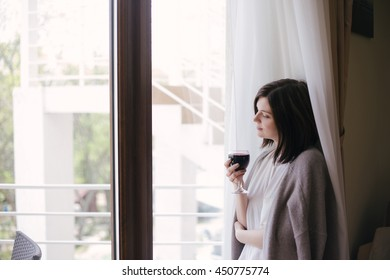 Young beautiful woman in a sweater drinking red wine near big window in a cozy room