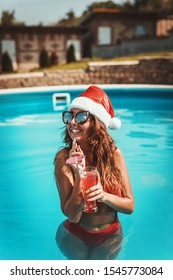 Young beautiful woman in the swimming pool in Santa Claus hat, is celebrating New Year and Christmas in hot country with glass of cocktail.