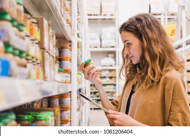 Young beautiful woman with a tablet picks baby food in a supermarket, the girl is studying the composition of the product close-up