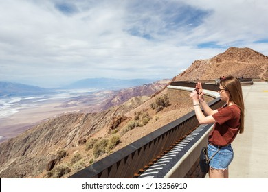 Young beautiful woman take a picture of Badwater Basin from Dante's View terrace in Death Valley National Park. California, USA