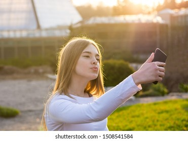 A young beautiful woman taking duck face selfie in a park at sunset