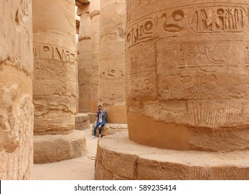 Young beautiful woman taking pictures between the columns of the hypostyle hall of Karnak's temple in Luxor, Egypt.