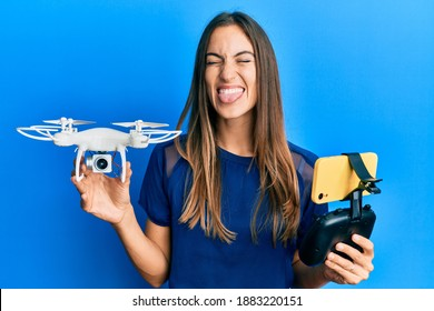 Young beautiful woman taking a selfie photo with smartphone flying drone sticking tongue out happy with funny expression.