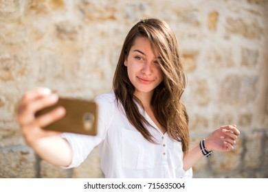 Young beautiful woman taking selfie and smiling