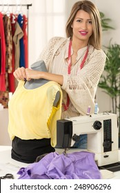 Young beautiful woman with tape measure draped over neck, leaning against the dressed mannequin, with a smile looking at the camera. Besides the mannequin on the table is a sewing machine.