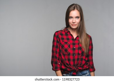 Young beautiful woman teenager in a red checked shirt and torn denim shorts on a gray background
