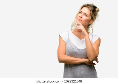 Young beautiful woman thinking and looking up expressing doubt and wonder