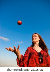 The young beautiful woman throws a red apple against dark blue sky.