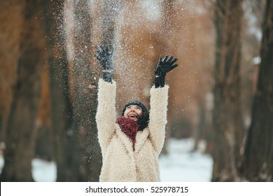 young beautiful woman throws snow over head