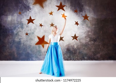 young beautiful woman took a star from the sky. Fantasy concept, Reach for the dream. A lot of gold stars, to dream and to set goals, Textured gray background