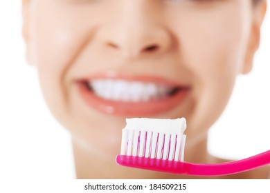 Young beautiful woman with toothbrush and paste. Focus on toothbursh. Isolated on white.