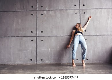 young beautiful woman in top and jeans dancing modern contemporary dance in the studio, contemporary art, harmony of body and soul, professional dancer