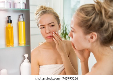 Young beautiful woman touching skin in bathroom. Unhappy girl standing in towel, looking in the mirror, checking dry irritated skin, puffiness and dark circles under eyes. Morning skincare routine.