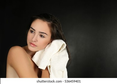 Young beautiful woman towel drying her hair after shower