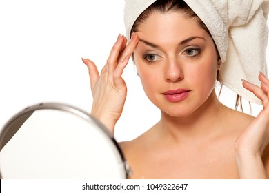 Young beautiful woman with towel on hr head on white background lifting her eyebrow with her finger
