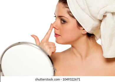 Young beautiful woman with towel on hr head on white background check her nose