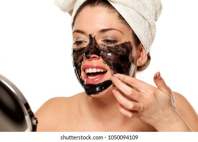 Young beautiful woman with towel on her head applying black mask on her face