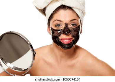 Young beautiful woman with towel on her head posing with black mask on her face