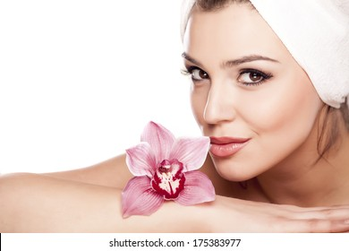 young beautiful woman with a towel on her head enjoying the scent of orchids