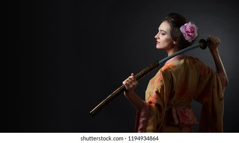 Young beautiful woman in traditional japanese kimono. Beautiful girl with japanese sword katana on a black background. Copy space.