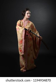 Young beautiful woman in traditional japanese kimono. Beautiful girl with japanese sword katana on a black background.