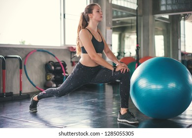 Young beautiful woman training pilates exercises with fit ball in fitness gym.